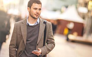Bausparen Informationsmaterial anfordern - junger Mann mit Smartphone