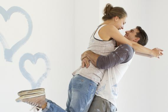 Couple painting blue hearts on wall