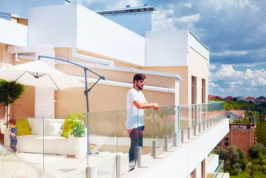 young adult man enjoying the view from rooftop patio