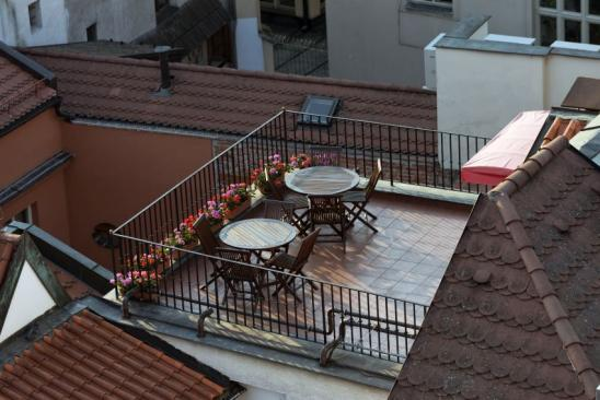 Bueautiful roof balcony with two tables and flowerbed on a tiled roof.