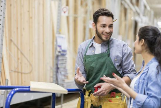 Handsome young male hardware store employee assists female customer with a lumber order.