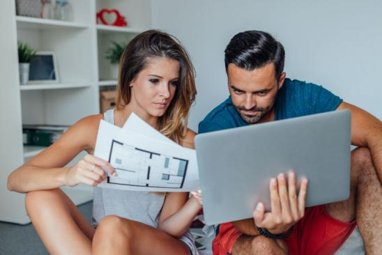 Young couple is using laptop pc while woman is holding architecture plans