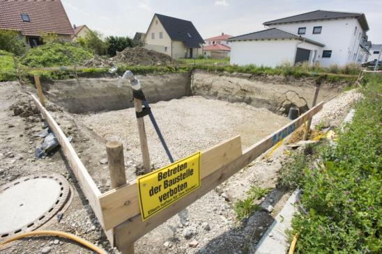 construction pit for foundation of residential house with sign in german language: keep off construction site - Parents are liable for their children