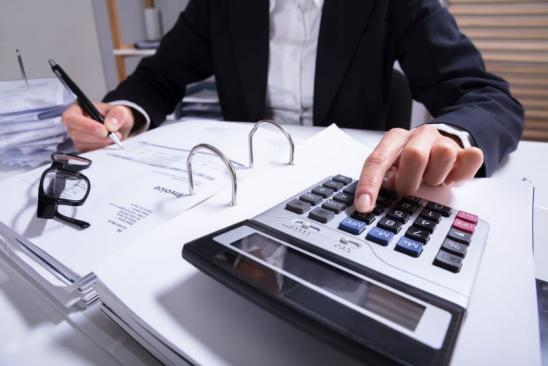 Midsection Of Businessperson Calculating Invoice With Calculator And Bills On Desk