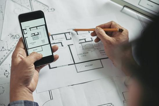 Hands of architect comparing blueprint on smartphone with another one on document in front of him