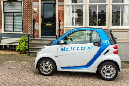 Amsterdam, The Netherlands - June 13, 2016: Amsterdam, The Netherlands - June 13, 2016: Car2Go Car Sharing Electrical Vehicle Parked in front a Brick House. Car2go provides carsharing services in European and North American cities. Car2go cars are user-accessed wherever parked via a downloadable smartphone app.