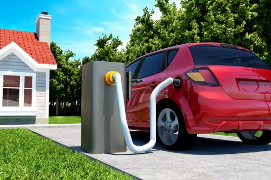 Electric car is connected by cable to charging station in front of a house. The battery of the car is getting refueled with power. There is a lawn in front of the house with grass and the sun is shining. The image is a 3D render.