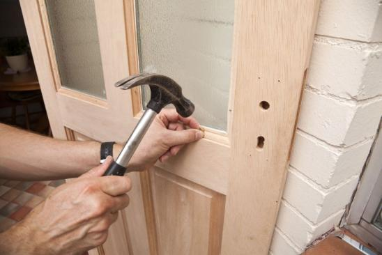 Glazier fixing beading to a hard wood door