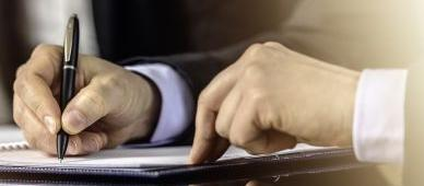 Close up of hands of a businessman signing contract.