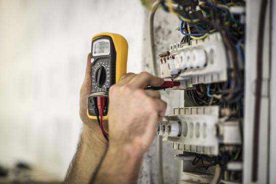 Detail shot of electrician testing voltage on a fuse box on construction site.