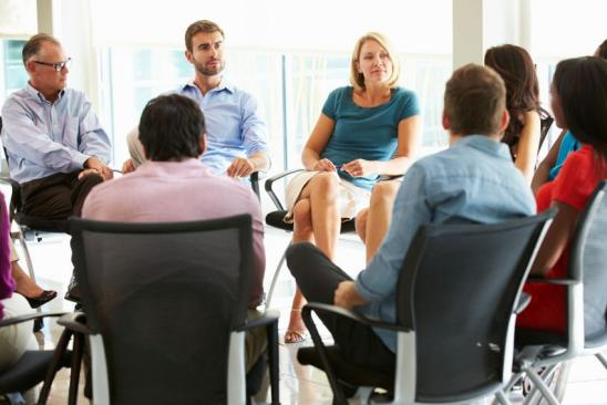 Multi-Cultural Office Staff Sitting Having Meeting Together In Smart/Casual Dresswear