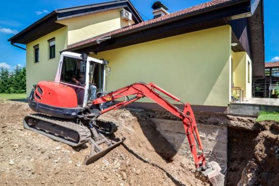 A family house is being rebuilt and renovated with the help of an excavator. Digger is digging dirt and excavating the basement.
