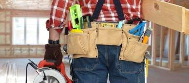 Builder handyman with tools on house renovation background.