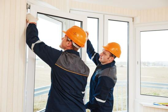 two windows installation workers installing double-glass pane