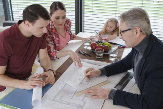 Architect explaining blueprint to couple in their home, daughter drawing at the table.