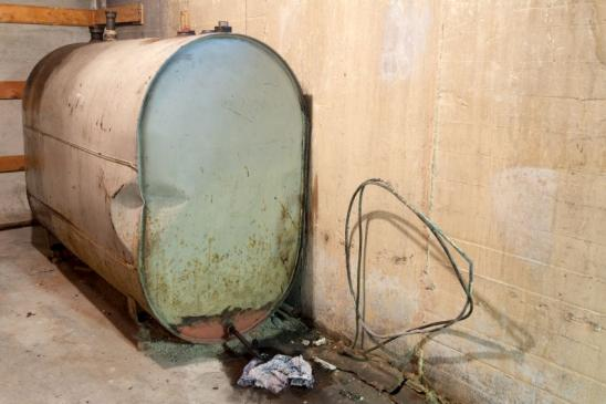 Old home heating oil tank in basement of residential home.