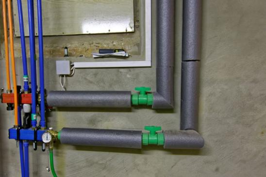 different colored pipes for warm water and heating, mounted on a cellar wall