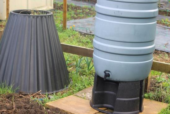 Photo showing a tall grey plastic water butt container (polypropylene) on a black stand, with a tap to fill up watering cans or connect to a hose pipe. The water butt is located on a patio of paving slabs, within a shared allotment vegetable garden. A cone-shaped plastic compost bin / compost heap is situated next to the water butt, being filled with composting garden waste and weeds.