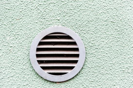 circular plastic air vent in white wall ventilation grille