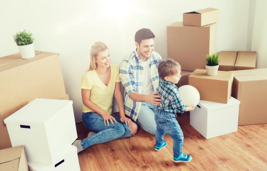mortgage, people, housing, moving and real estate concept - happy family with boxes playing ball at new home