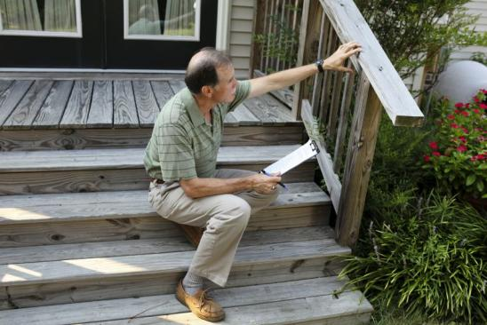 An adult male inspects a wooden deck railing.