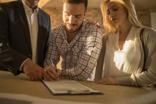 Unrecognizable investor showing young couple where to sign the contract for buying a house.