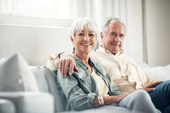 Portrait of a happy elderly couple relaxing together on the sofa at home