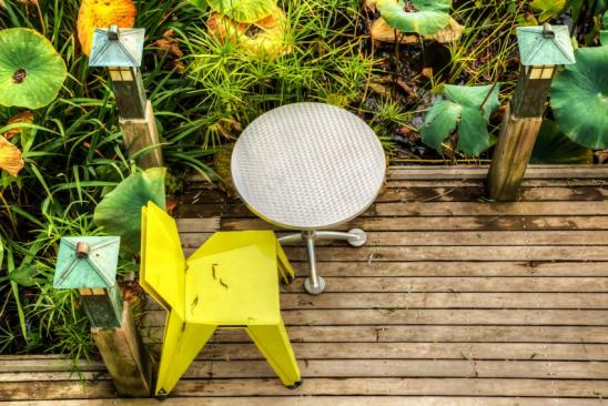 Yellow chair and metal table on a deck surrounded by plants at a garden