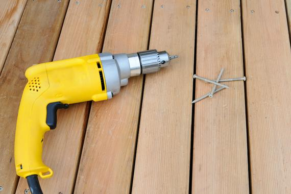 Electric drill and screws on cedar deck.