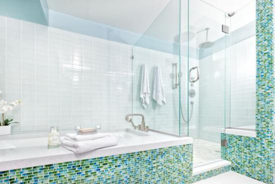 Subject: Contemporary residential home bathroom modern design featuring glass shower stall, bathtub, and glass wall tiles. Photographed in horizontal format with copy space.