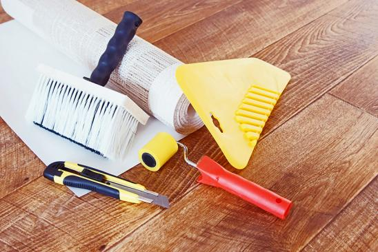 Tools for wallpapering and a roll of wallpaper lie on wooden floor