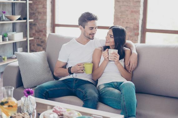 True love. Beautiful couple in casual outfit is sitting on modern sofa and smiling. They are drinking mugs of tea and look at each other with tenderness