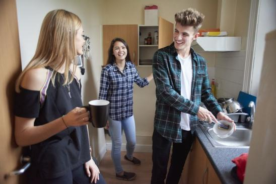 male and female university student chat whilst having a brew of tea in their student flat . The young man is doing the dishes , whilst chatting to the two female flatmates. They are all standing and laughing .