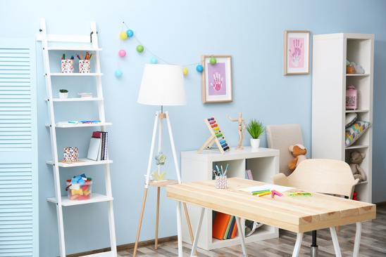 Wooden table in blue children room interior