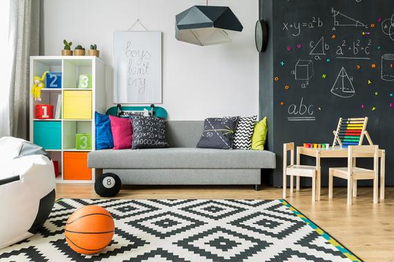 Shot of a schoolboy room with a grey sofa and big blackboard