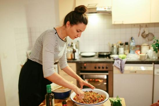 Young woman preparing oriental food in the kitchen at home, cus cus and hummus, with wine.