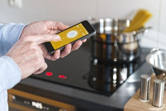 Close-up of man's hand holding mobile phone, thanks to smart home control mobile application a man is setting induction hob or cooker and oven; kitchen interior.