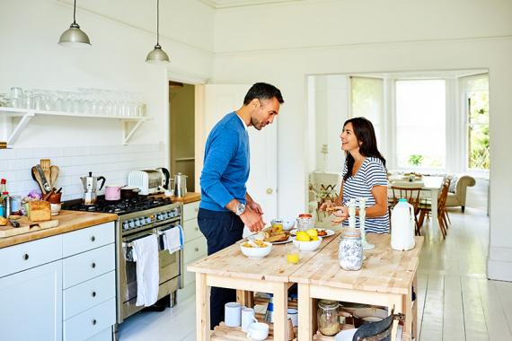 Portrait of a happy pregnant couple standing together in kitchen and preparing breakfast.