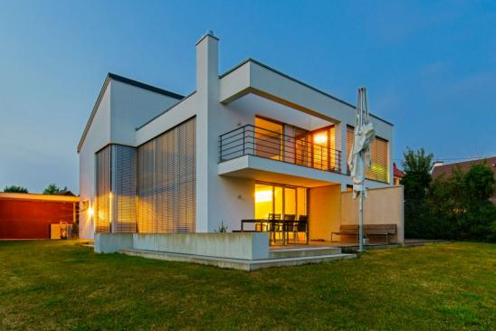 Modern Architecture House with large window front and closed aluminium shutters illuminated at twilight under blue cloudless summer sky. Made with Sony A7RII - full owner property released.